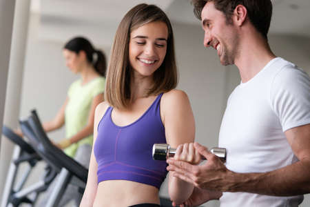 Smiling young woman and personal trainer with dumbbells in gym