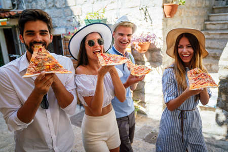 Group of friends eating pizza while traveling on vacation Stockfoto