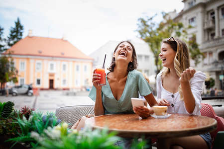 Technology, friendship and people concept. Happy young women with smartphone at outdoor cafe