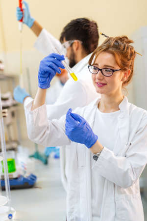 Serious clinicians studying chemical elements in laboratory