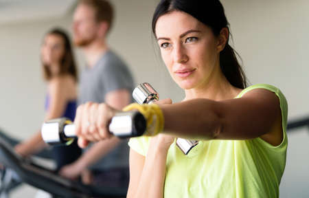 Happy fit fitness girl exercising indoor in fitness center.