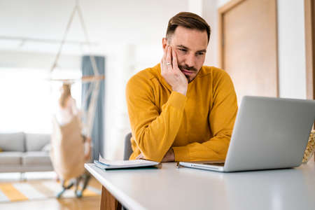 Upset young man counts family budget on laptop