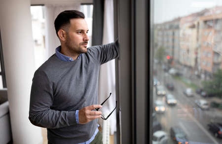 Portrait of man sad and depressed standing at window in despair at home