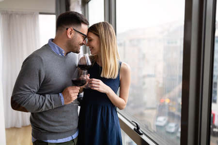 Cheerful happy couple in love drinking wine and having romantic date 版權商用圖片 - 157344865