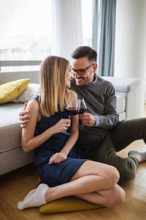 Cheerful happy couple in love drinking wine and having romantic date 版權商用圖片