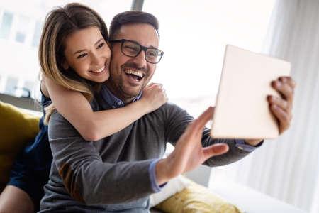 Happy couple in love having fun with digital tablet 版權商用圖片