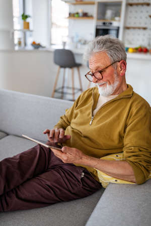 Technology, people and lifestyle concept. Senior man with tablet pc computer relaxing at home
