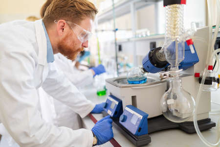Research scientist looking at reaction in test tube in laboratory