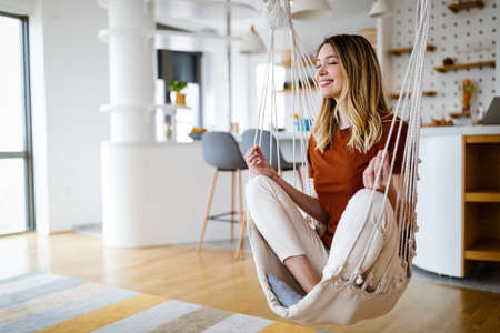 Young woman chilling at home in comfortable hanging chair in front of big window. Foto de archivo