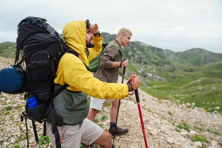 Group of friends with backpacks doing trekking excursion on mountain 版權商用圖片 - 157342777