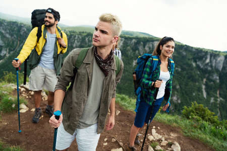 Group of happy friends with backpacks hiking together 版權商用圖片 - 157341493
