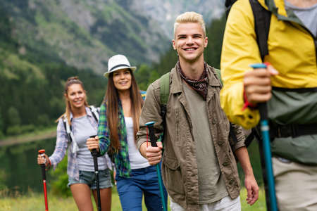 Group of young friends hiking in countryside. Multiracial happy people travelling
