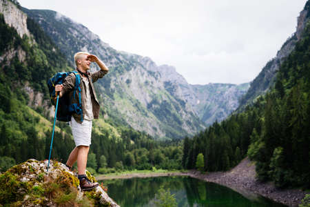 Handsome happy backpacker man hiking, camping through mountain forest. 版權商用圖片 - 157342590