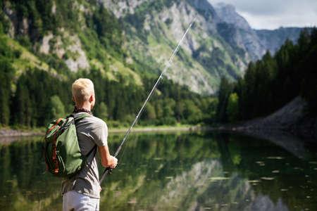 Fisherman fishing in nature at lake while camping outdoor 版權商用圖片