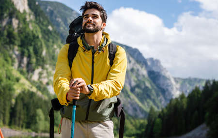Hiker young man with backpack and trekking poles looking at the mountains in outdoor 版權商用圖片 - 157342472