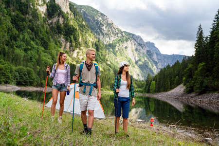Adventure, travel, tourism, hike and people concept. Group of happy friends with backpack outdoors