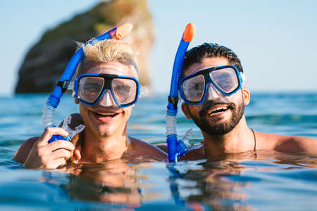 Happy friends enjoying summer vacation, travel during scuba diving.