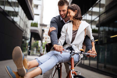 Portrait of happy young couple riding a bike and having fun together outdoor Banco de Imagens