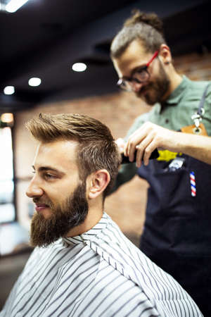 Young bearded man getting haircut by hairdresser while sitting in chair at barbershop Stock Photo