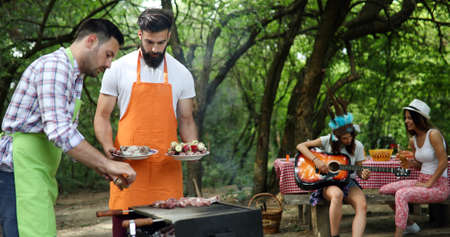 Friends making barbecue and having lunch in the nature