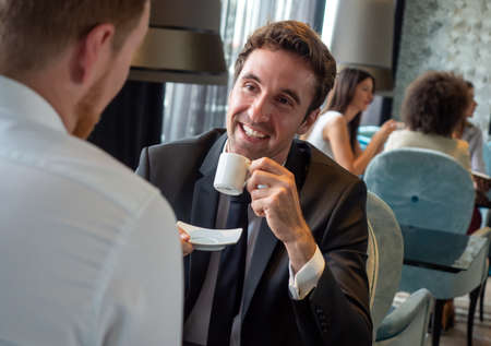 Colleagues and friends. Two cheerful businessmen drinking coffee and talking to each other