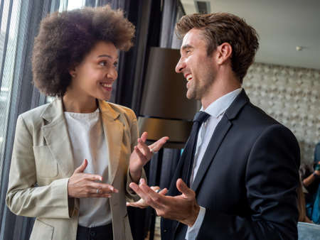 Happy business colleagues talking in modern office