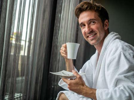 Young man in bathrobe drinking coffee at home 版權商用圖片