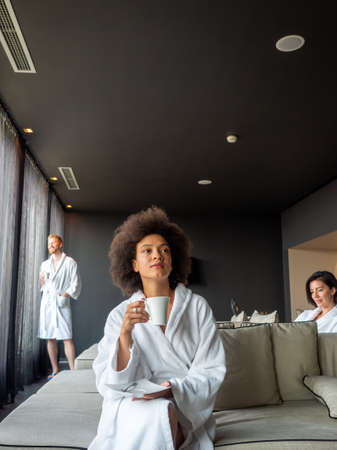 Beautiful black woman relaxing at luxury hotel spa wearing bathrobe and drinking coffee