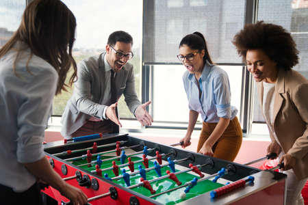 Coworkers playing table football on break from work