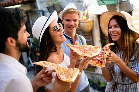 Group of friends eating pizza while traveling on vacation 版權商用圖片