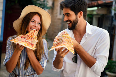 Group of friends having fun outdoor,eating pizza