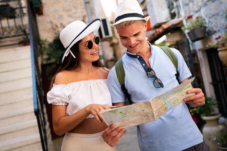 Happy young couple of travellers holding map in hands