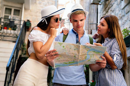 Happy traveling friends tourists sightseeing with map in hand 版權商用圖片