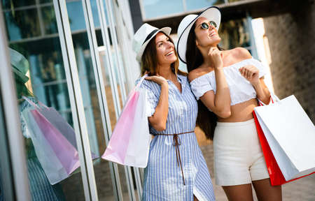 Sale, consumerism, shopping and people concept. Happy young women with shopping bag 版權商用圖片