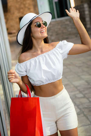 Beautiful girl is holding shopping bags and smiling while walking down the street