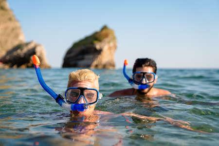 Happy friends men enjoying summer vacation and scuba diving