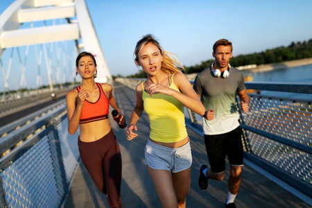 Fitness, sport, people and running concept. Happy fit friends running outdoors