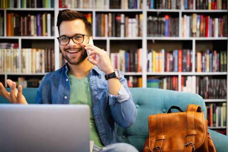 Cheerful smiling man talking on phone and working, studying on laptop