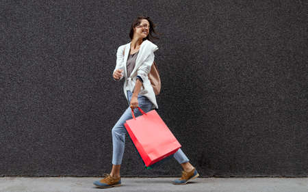 Portrait of beautiful smiling young woman with shopping bags
