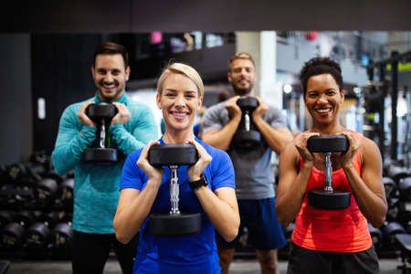 Attractive sports people friends are working out in gym Standard-Bild