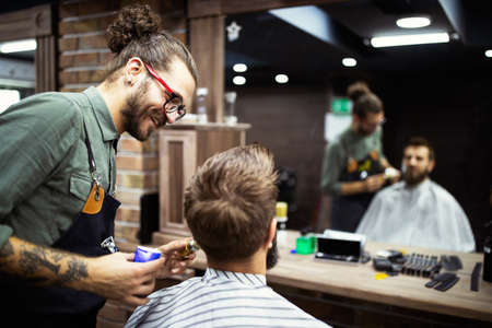 Client during beard shaving in barber shop Standard-Bild