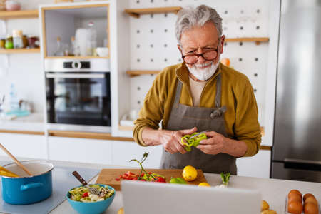 Mature handsome man cooking in home kitchen