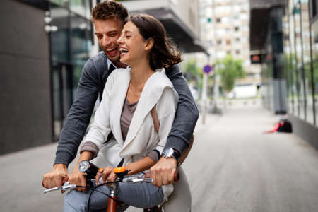 Portrait of happy young couple riding a bike and having fun together outdoor 스톡 콘텐츠