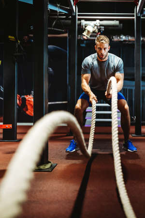 Fitness man working out with battle ropes at gym.
