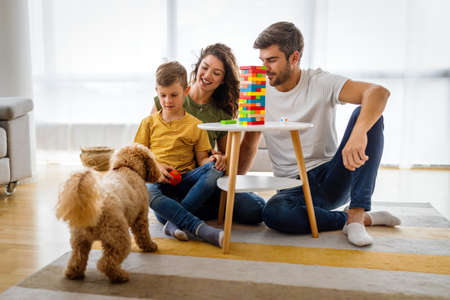 Happy family playing, having fun with dog at home