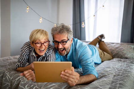 Happy smiling mature couple using digital tablet at home