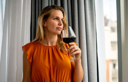 Beautiful young woman with glass of red wine standing near window 版權商用圖片