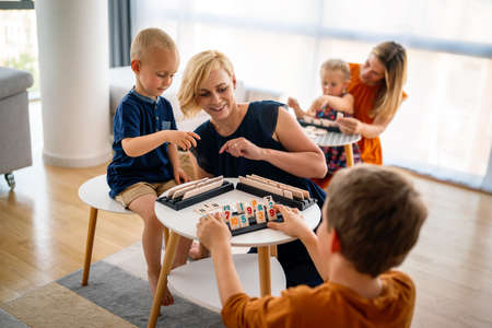 Children and woman learn while playing a board game. Education, fun, children concept
