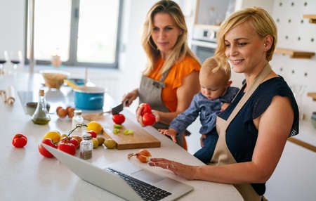 Happy lesbian couple with child preparing food at home together