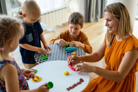 Family activities in the kids room. Woman and children playing together.